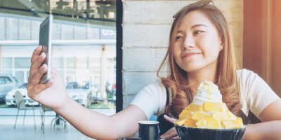 An asian woman using smart phone before eat Bingsu