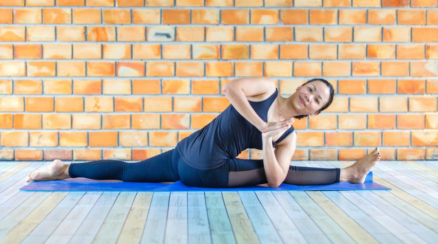 Asian trainee strong woman practicing difficult yoga pose in a concrete background