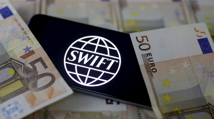 Swift code bank logo is displayed on an iPhone 6s on top of Euro banknotes