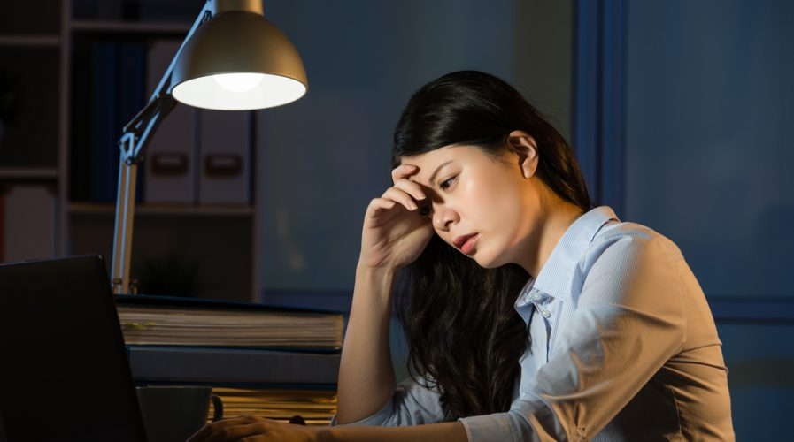 asian business woman sitting at desk sleepy working overtime late night