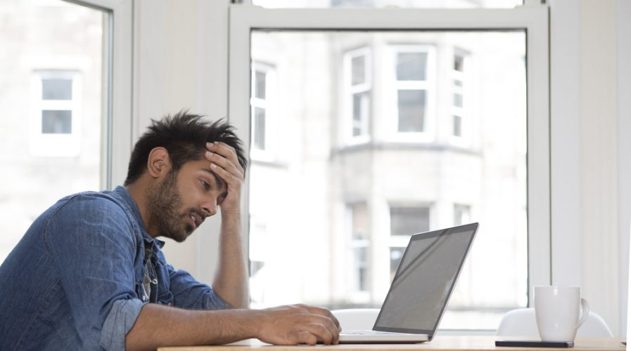Stressed and frustrated Asian man sitting at his laptop