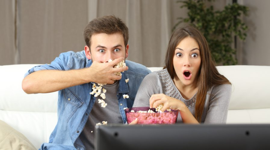 Amazed couple watching tv program sitting on a couch at home