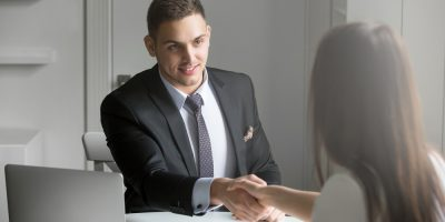 businessman and businesswoman handshaking over the office desk