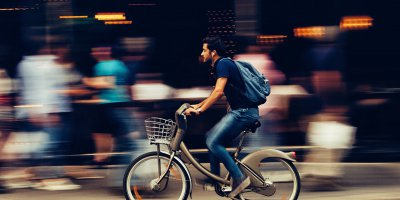 man riding a bicycle in a crowded city