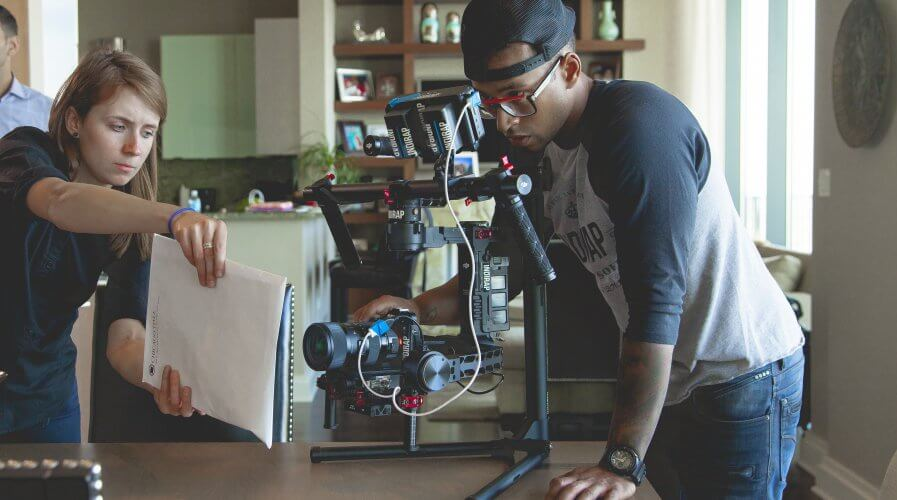 man recording a video of a product, assisted by a women