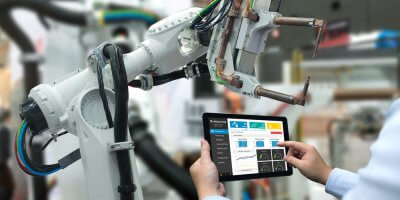 Engineer hand using tablet, heavy automation robot arm machine in smart factory industrial with tablet real time monitoring system application