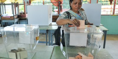 a woman casting a ballot into the ballot box