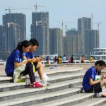 People sit on steps against a backdrop of residential buildings under construction, in Haikou, Hainan province, China