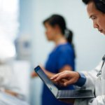 a doctor looking at patient information on a laptop