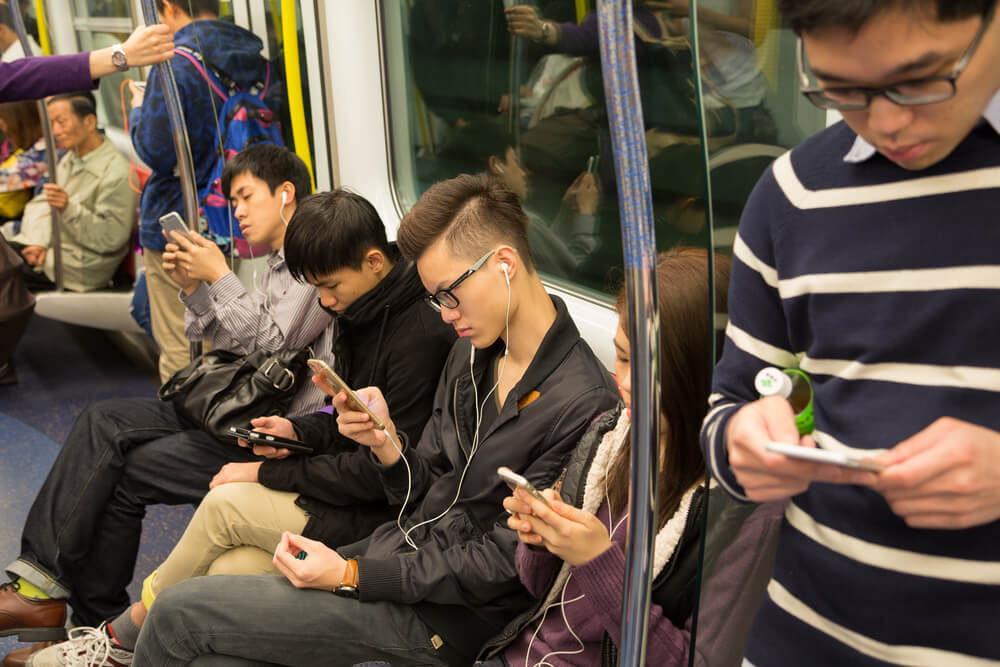 a group of people looking at their phone in the train