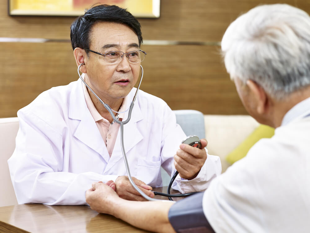 a doctor checking the blood pressure of an elderly man