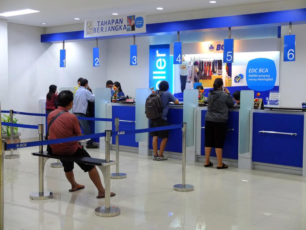 customers waiting at a bank teller
