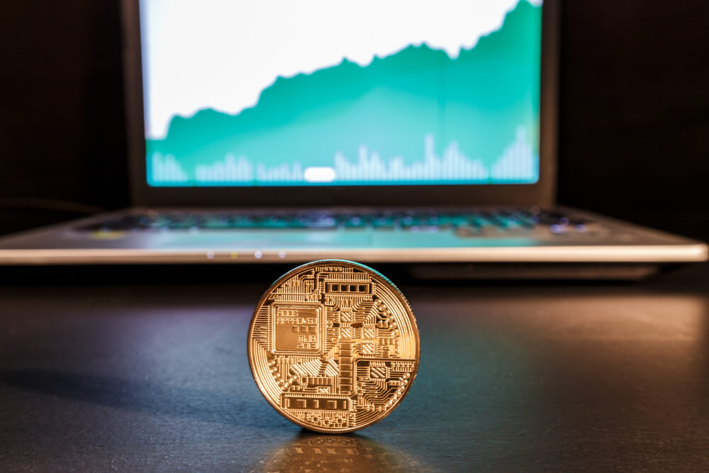 a cryptocoin in front of a computer