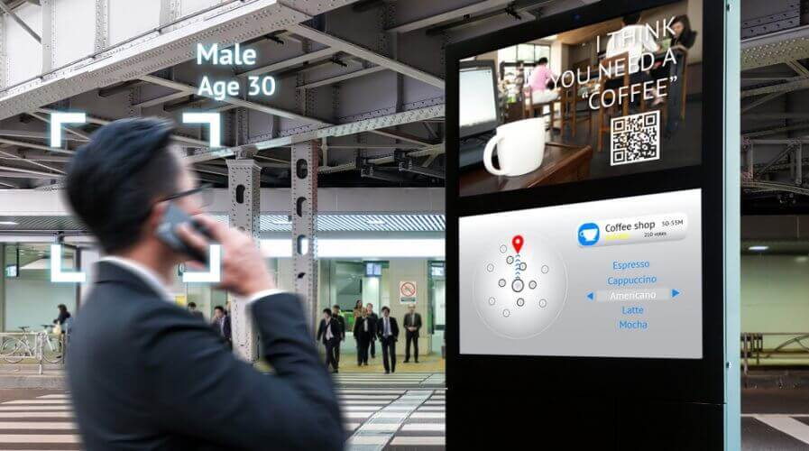 a man looking at a targeting advertising on a digital signage