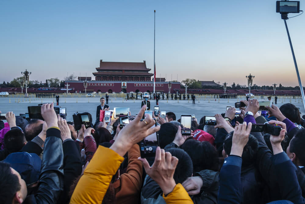 people with mobile phones waiting outside Tiananmen square