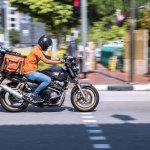 A food delivery worker was riding a motorbike on a street