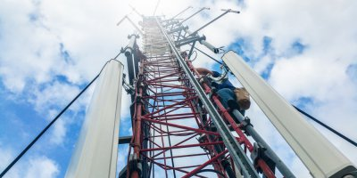 a worker climbing up a communications tower