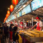 a busy street in china, where vendors are selling food