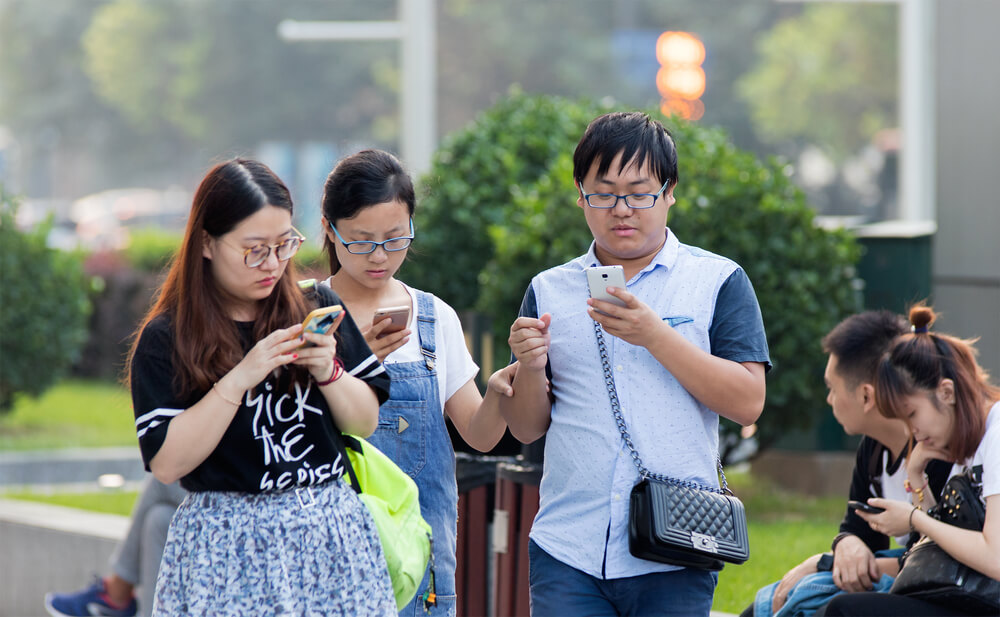 a group of people using their phones in public