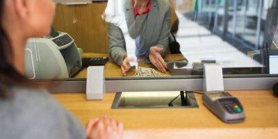 a bank teller helping a customer make payments