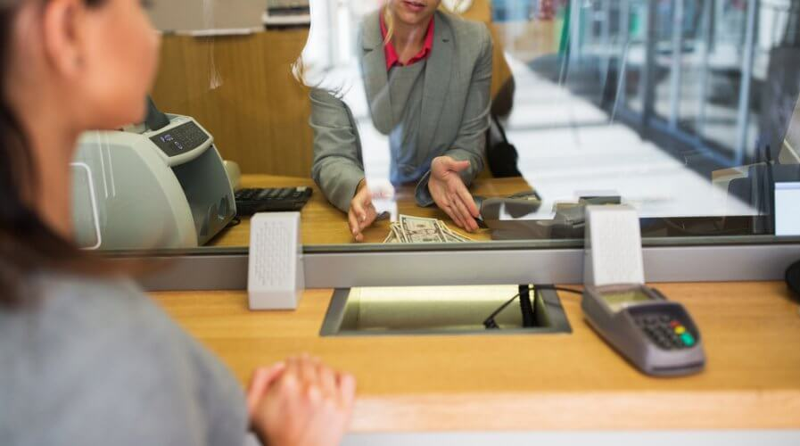 a bank teller helping a customer make payments