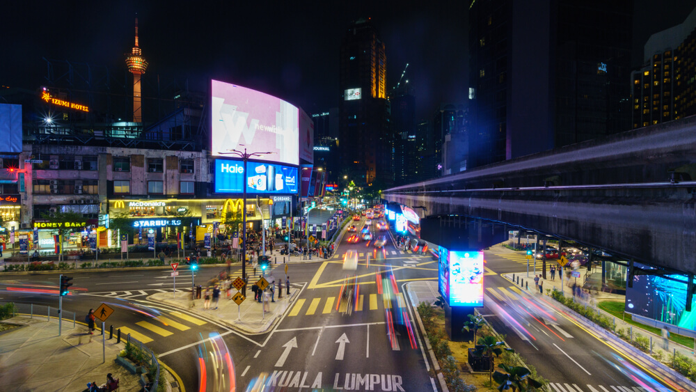 a busy intersection in Malaysia filled with billboards