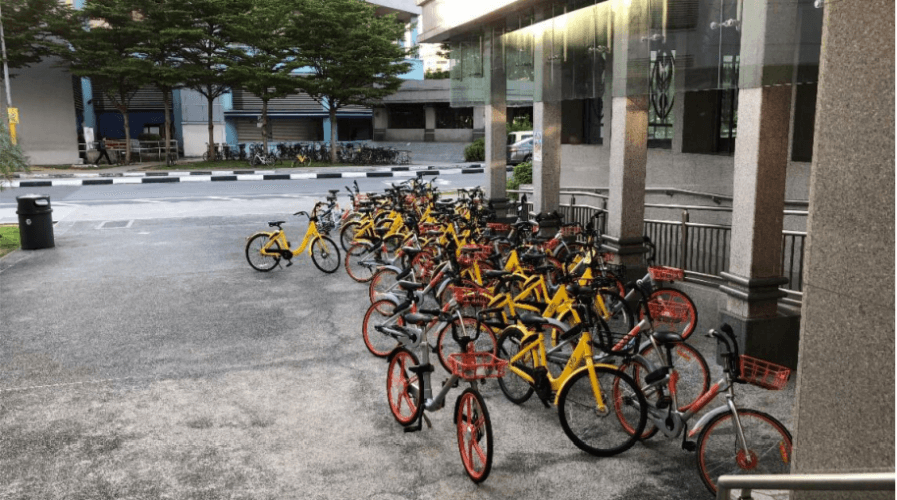 bikes being parked haphazardly near an MRT station
