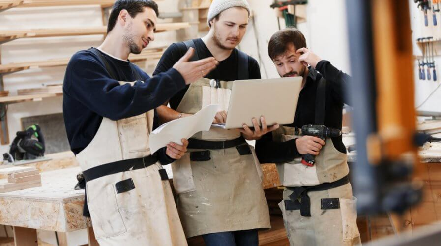 a small carpentry team looking at a laptop