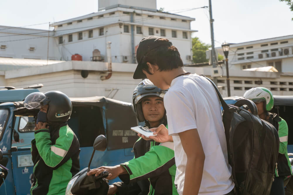 a go jek user getting picked up by a rider