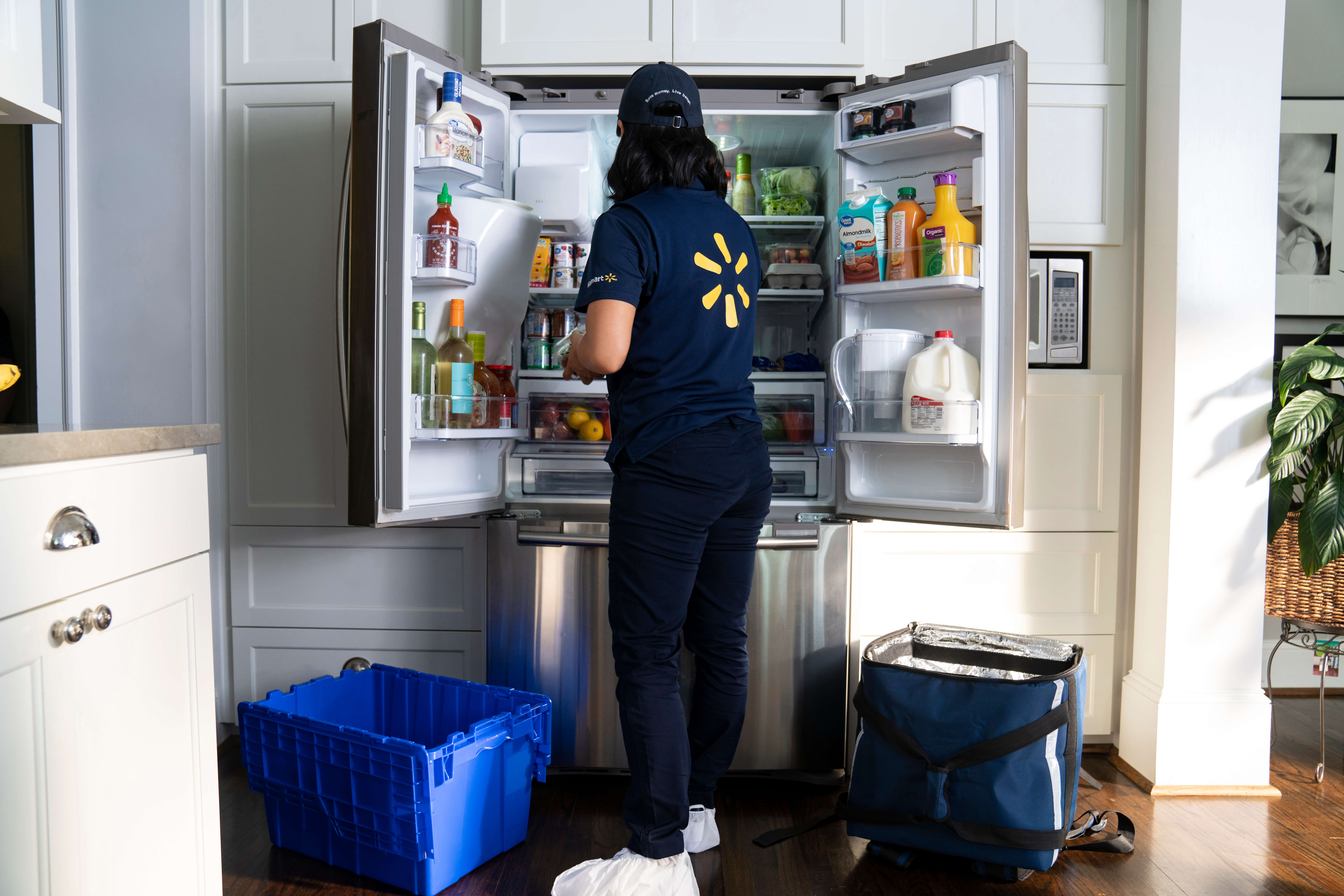 Walmart associate stocking a fridge with InHome Delivery. Source: Walmart