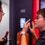 An Alibaba employee helps a customer at a facial recognition check-out booth. Source: AFP.