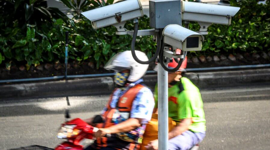 A closed circuit TV (CCTV) system is seen as a motorcycle taxi rider ferries a passenger in Bangkok. Source: AFP