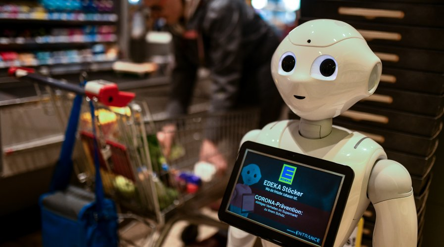 A humanoid robot at the cash desk of a supermarket.