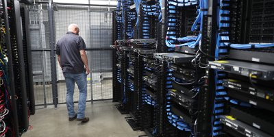 A man works among the racks and switches in a data center. Source: AFP.