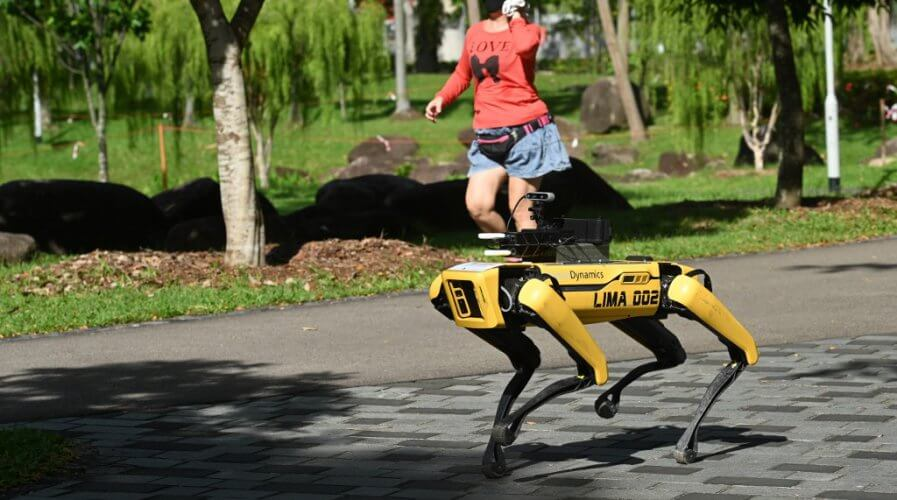 Boston Dynamics Robot Spot in a park in Singapore, broadcasting a recorded message reminding people to observe safe distancing.