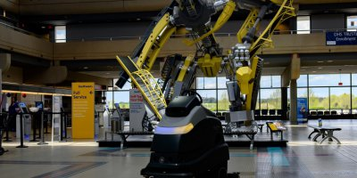 A UV floor cleaning robot cleans the floor near the ticketing windows at Pittsburgh International Airport.